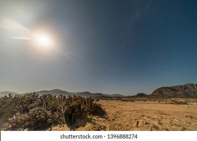 "Milky way full moon nightscape at Atacama Desert coastal area. White sands at ""Playa Blanca"" beach in Pan de Azucar National Park the amazing Atacama Desert sands ending on the Pacific Ocean beach"