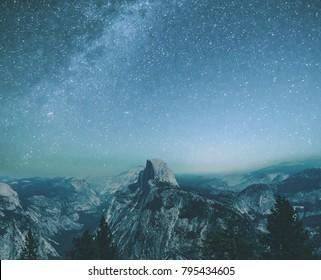 Milky Way, galaxies, and stars over the Half Dome in the dark night sky, with waterfalls and forests in the valley, taken from Glacier Point, Yosemite National Park, California, United States.