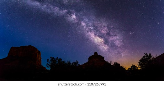 The Milky Way Galaxy arcs across the sky from Bell Rock over Courthouse Butte, to the left, on a dark night near Sedona, Arizona.
