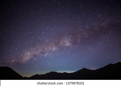 Milky Way Galaxy and many stars rise over the sky at the forest in Mt.Bromo, Indonesia. (Visible noise due to high ISO, soft focus)