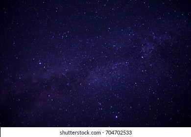 Milky Way galaxy, night stars blue and purple sky photography. Night landscape in long exposure. Deep colors sky with magic lightning view on the horizon line scenery, beautiful cover