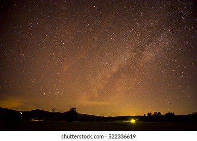 Milky Way galaxy, on rice paddy fields and mountains. Long exposure photograph, with grain.Image contain certain grain or noise and soft focus.