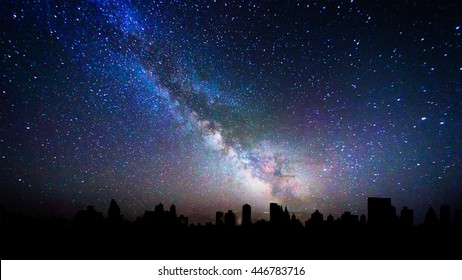 Milky way galaxy over a city skyline silhouette