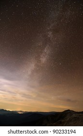 milky way galaxy over mountain ridges and clouds