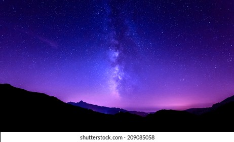 Milky Way Galaxy. Purple night sky stars above mountains