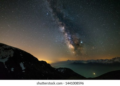 Milky way galaxy stars over the Alps, Mars and Jupiter planet, snowcapped mountain range, astro night sky stargazing