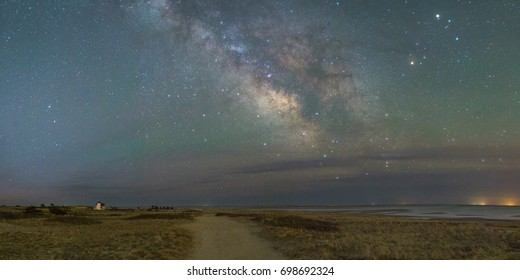 The Milky Way Galaxy viewed from Harding's Beach in Chatham, Massachusetts with Stage Harbor Lighthouse in the distance.
