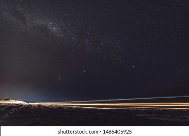 Milky way glows in a starry night sky in Broome. There is also a car light trail due to the long exposure effect. Australian night sky is a must for astronomy lovers. South hemisphere constellations