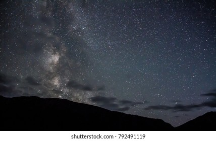 Milky way hidden behind clouds above mountain top