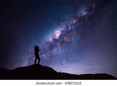 Milky Way landscape. Silhouette of Happy woman taking a bright star photograph.