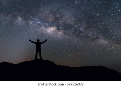 Milky Way landscape. Silhouette of Happy man standing on top of mountain with night sky and bright star on background.