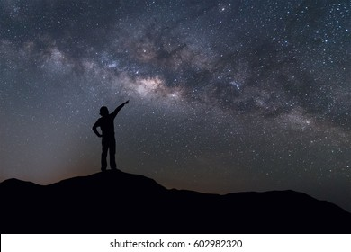 Milky Way landscape. Silhouette of Happy woman standing on top of mountain with night sky and bright star on background.