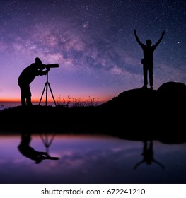 Milky Way landscape. Silhouette of photographer and happy man standing on top of mountain with night sky and bright star on background.