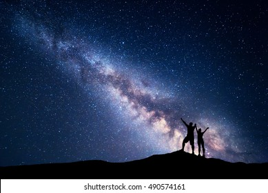 Milky Way. Night sky with stars and silhouette of standing happy man and woman with raised  up arms on the hill. Blue milky way with people on the mountain. Background with universe. Night landscape