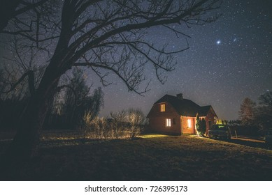 The Milky Way in night sky with stars over wooden country house at night. Latvia - vintage film look