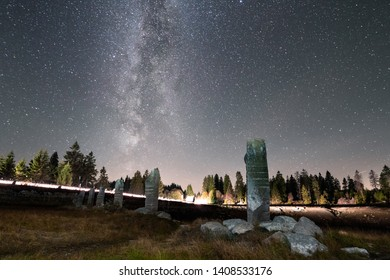 Milky way in the night sky with traces of Light on the horizon, the Harz national Park, Oderteich lake