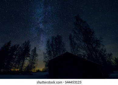 Milky way, old barn and trees in night landscape