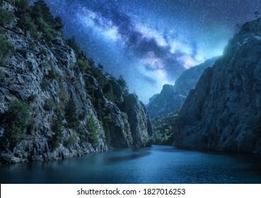 Milky Way über den schönen Berg Canyon und blaues Meer in der Nacht im Sommer. Farbige Landschaft mit hellSternenhimmel mit Milchstraße, Felsen, Bäumen, Mondschein, Sternbild. Galaxie. Natur und Raum