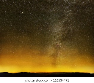 Milky way over black mountains and yellow city lights on starry sky