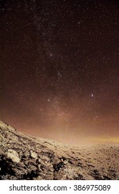 milky way over clouds and snowy hills