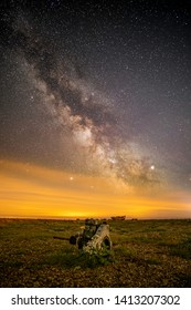 Milky Way Over Dungeness Kent, showing shingle stones orange cloud and scrap car axle part