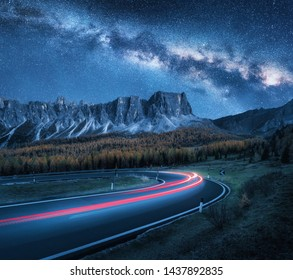 Milky Way over mountain road at night. Blurred car headlights on winding road in autumn. Beautiful landscape with blue starry sky with milky way, light trails, rocks, trees and highway in fall. Space