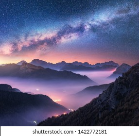 Milky Way over mountains in fog at night in summer. Landscape with alpine mountain valley, purple low clouds, colorful starry sky with milky way, city illumination. Passo Giau, Dolomites, Italy. Space
