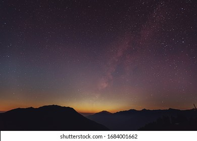 Milky Way over the mountains of the Himalayas at the time of the transition from day to night. High rocks with snowy peak and sky with stars. Night landscape with the bright galaxy in Langtang Nationa