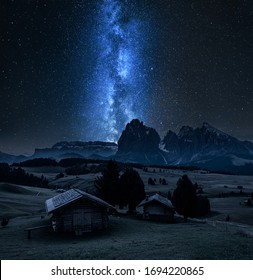 Milky way over wooden huts in Alpe di Siusi, Dolomites