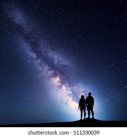 Milky Way with people on the mountain. Landscape with night sky with stars and silhouette of standing  man and woman. Milky way with couple. Travelers against beautiful galaxy. Universe