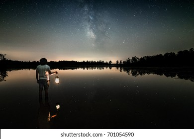 The Milky Way rises over Oswego Lake in the New Jersey Pine Barrens while a man holds a kerosene hurricane lantern while wading in the water