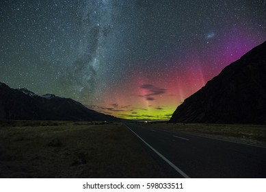 Milky Way rising above highway near Tekapo New Zealand with Aurora Australis Or The Southern Light Lighting Up The Sky . Noise due to high ISO; soft focus / shallow DOF due to wide aperture used.