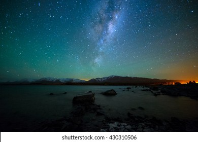 Milky Way Rising Above Lake Tekapo, New Zealand with Aurora Australis Or The Southern Light Lighting Up The Sky . Noise due to high ISO; soft focus / shallow DOF due to wide aperture used.