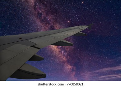 milky way seen from an airplane with a wing in the foreground