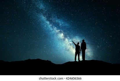 Milky Way with silhouette of a family. Father and a son who pointing finger in night starry sky on the mountain. Night landscape. Beautiful Universe. Space. Travel background with sky full of stars