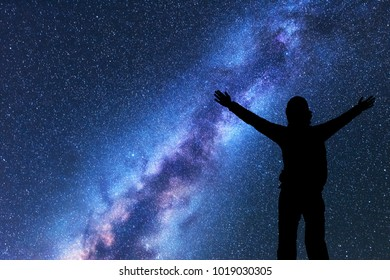 Milky Way with silhouette of a happy woman with backpack and raised up arms at night. Space background with sky with stars, bright colorful milky way, girl. Success. starry sky and woman. Night scene