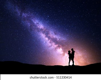 Milky Way with silhouette of people. Landscape with night starry sky. Standing man and woman on the mountain with yellow light. Hugging couple against purple milky way. Beautiful galaxy. Universe.