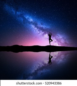 Milky Way. Silhouette of a standing woman practicing yoga on the mountain near the pond with sky reflection in water. Landscape with meditating girl on the hill. Night starry sky and milky way
