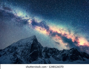 Milky Way and snowy mountains. Space. Beautiful scene with snow covered rocks and starry sky at night in Nepal. Mountain ridge and sky with stars in Himalayas. Landscape with bright milky way. Galaxy