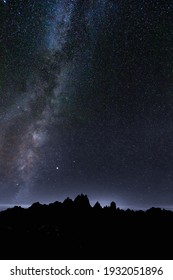 Milky Way and Starry Sky in the Mountains. Milky way galaxy. Long exposure photograph.With grain. Starry night sky with the milky way seen from the coast with vegetation in the foreground.