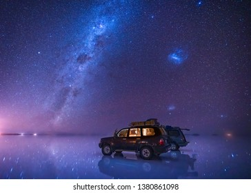 milky way and starry sky over the salt flat of Uyuni, Bolivia, with 2 SUVs parked on the reflective lake surface.