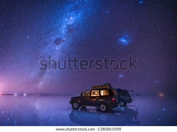 ボリビアのウユニの塩の平らな地面に天の川と星の空、反射する湖面に2つのSUVが停止している。