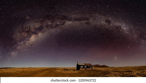 The Milky Way stretches of an abandoned hut in the Australian outback