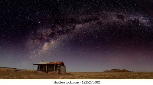 The Milky Way stretches over an old abandoned hut in the middle of the Australian outback