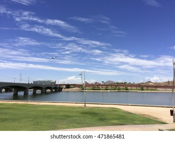 Mill Avenue Bridge over Sail River Lake with jet airliner in the sky heading for Phoenix airport, Tempe, AZ.