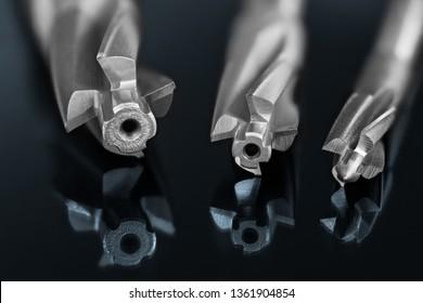 Mill cutters. Drill bit. Artistic detail. Mirroring in glass. Steel countersink cutting tools set. Decorative still life. Dark shiny background. Beautiful blue reflection. Metal machining instruments.