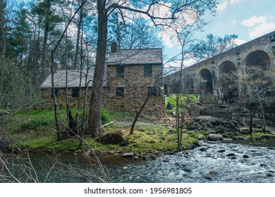The mill house lodge behind the bridge with the dam along the stream backside of the historic stone building in the Cumberland mountain state park on a bright sunny day in spring