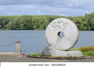 Mill Menesca. Minsk. Belarus. 08/15/2019. Millstone wheel sculpture. The area of the former Perespy River. The founding place of the city of Minsk. Progressive Street. Bank of the river Svisloch