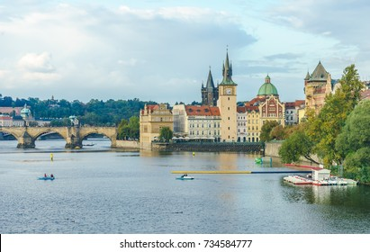 The Mill peninsula and the Charles Bridge in Prague in the Czech Republic at sunset. Boats on the Vltava River