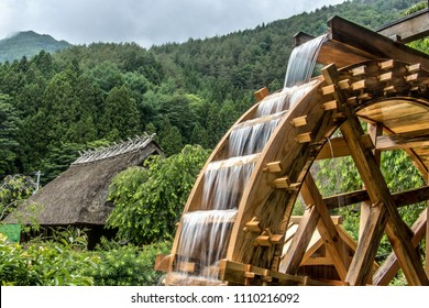 The mill wheel rotates under a stream of water, open air museum at village with traditional thatched roofed houses